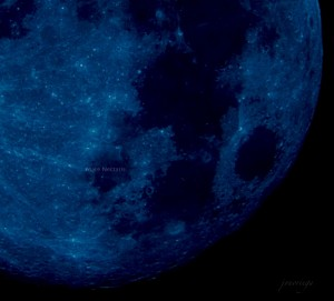 Closeup of moon showing craters and dark areas, all in indigo colors.