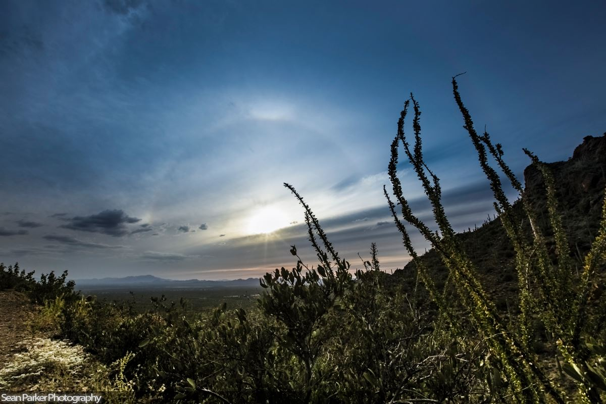 Half a sun halo above a horizontal cloud over desert landscape.