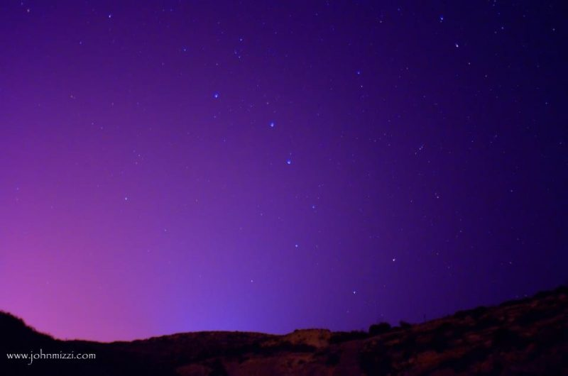 Big Dipper with other stars in a purple sky over low hills.