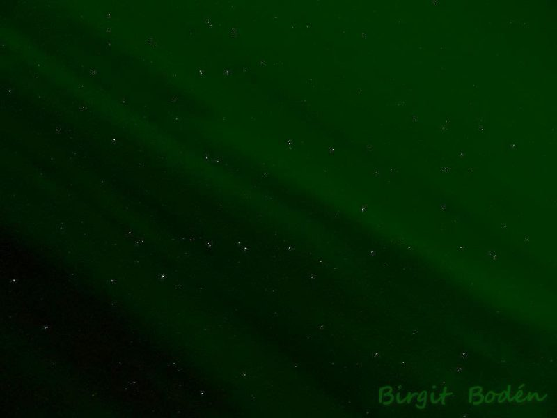 Big Dipper seen through swaths of translucent green in the sky.