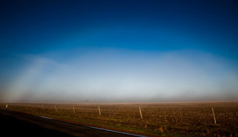 Pale arc over fog over brown stubbly field past a wire fence.