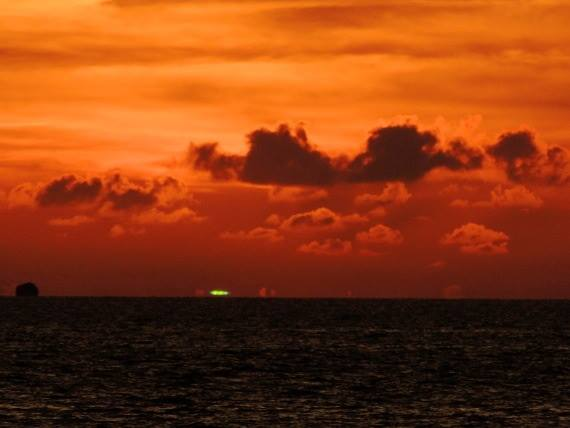 Dark sea, cloudy orange sunset sky, short green stripe right on horizon.