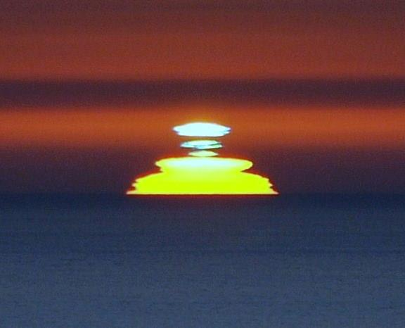 Dark blue ocean, wide yellow sun with short, bright stripes above it.