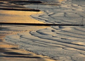 WAter lapping in from the right side over a beach lightly illuminated in golden hues.