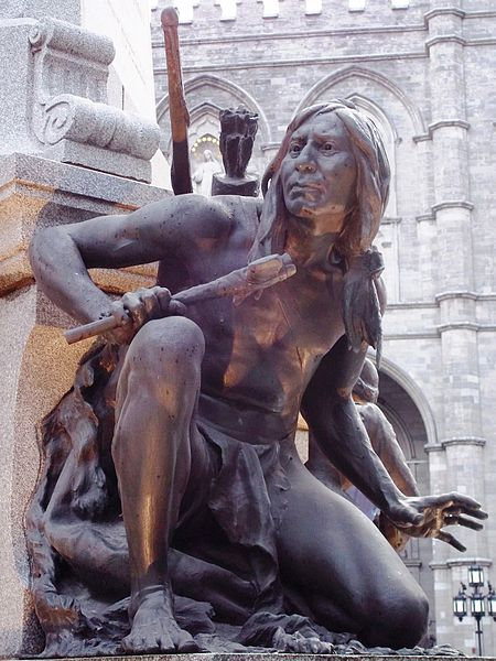 Bronze statue of crouching Native American man in loincloth clutching a stick.