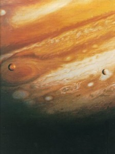 Jupiter, its Red Spot, its banded atmosphere, and two of its moons in this view taken by the Voyager 1 spacecraft from about 20 million kilometers (12 million miles) away.  Each moon is about the size of Earth's moon.  Meanwhile, Jupiter could contain more than a thousand Earths.  The visible moons here are Io (left), is in front of the Red Spot, and Europa (right).