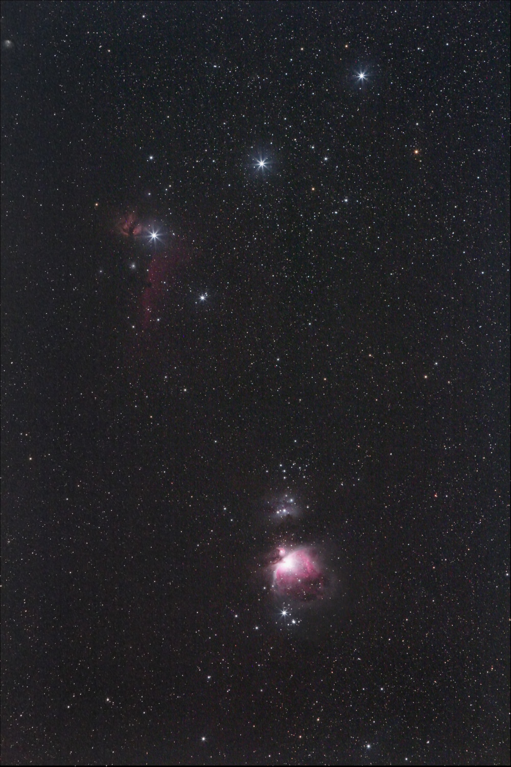 Star field with three bright stars in a row and a small but distinct pink nebula below.