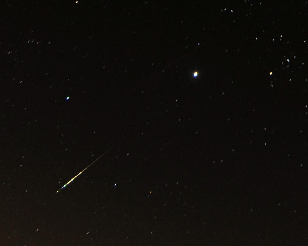 Starry sky with thin, bright yellow streak heading away from V-shaped group of stars.