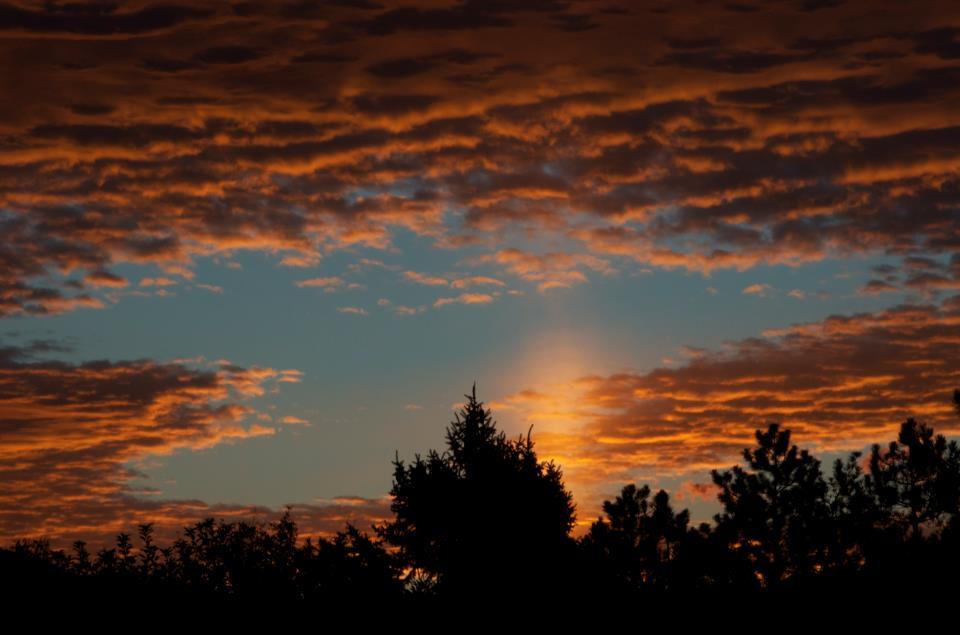Short, wide verical column of light in open blue sky between red-orange clouds.