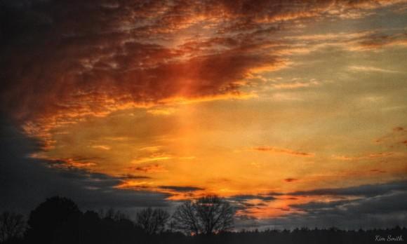 Vertical column of light amid majestic orange sunset clouds.