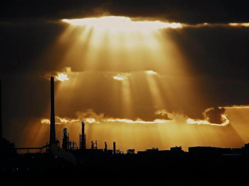 Orange rays coming down from black clouds over a dark silhouette of industry.