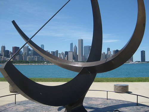 Crossed semicircular bars mounted on pedestal casting shadow; Chicago skyline in distance.