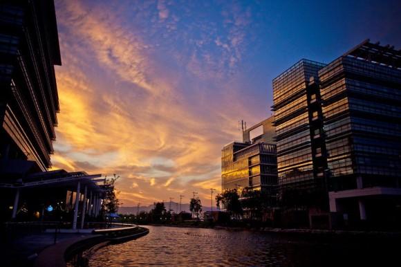 Yellow sunset clouds between medium height modern buildings.