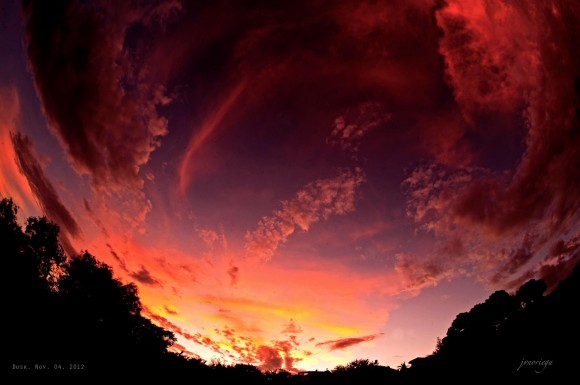 Circular panorama of sky filled with red sunset clouds.
