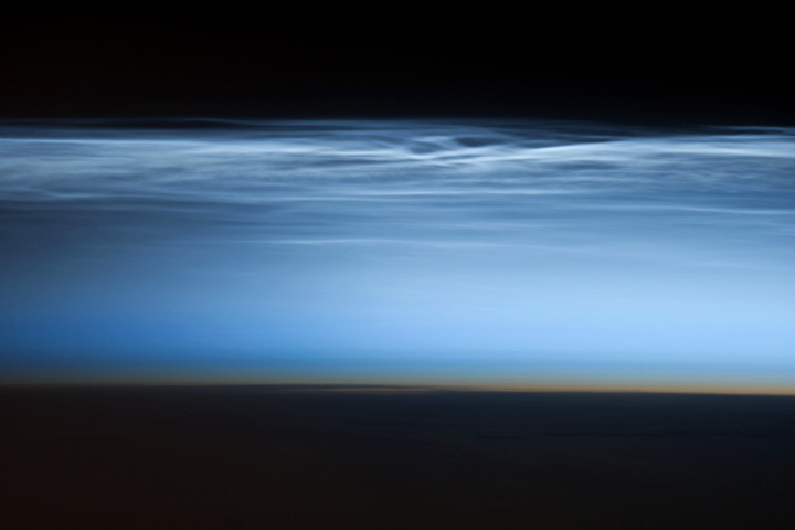 Black space, shining ripply layer of clouds, dark orange narrow stripe above black silhouette of Earth.