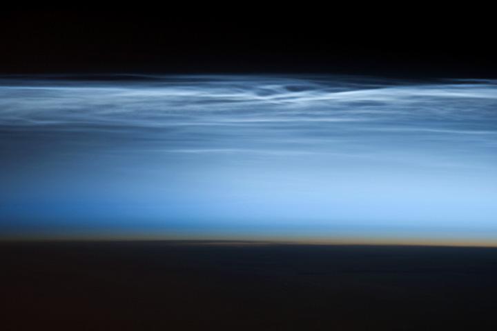 Black space, shining layer of clouds, dark orange narrow stripe above black silhouette of Earth.