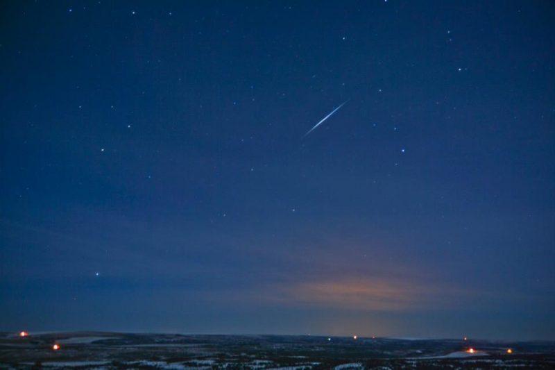 Dark blue starry sky with short, very bright streak above almost level horizon.