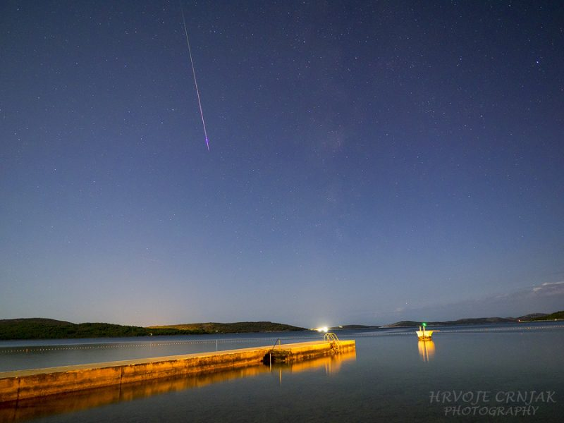 Bright streak of light over pier on lake, in dark blue sky with stars.