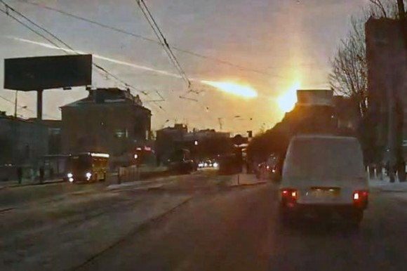 Extremely bright ball in the sky with explosion behind it over city street.