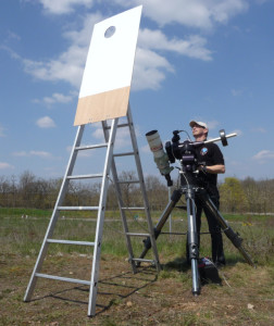 Man standing with telescope looking at sunshade with a hole for viewing the moon in the daytime sky.
