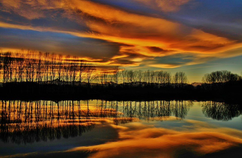 River lined by trees reflecting cloudy red sunset.
