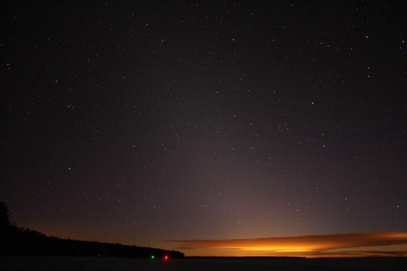 Orange clouds on horizon; tall, fuzzy oblique triangle of light; some stars visible.