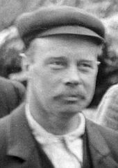 Victorian-looking man with a mustache and flat cap.