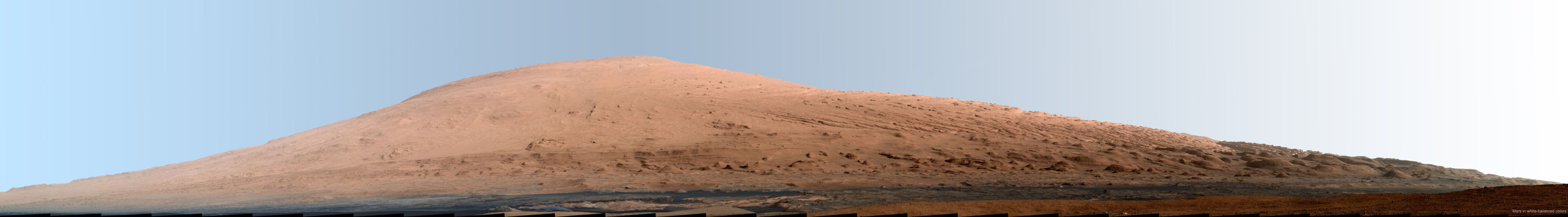 Mosaic of images from NASA's Mars rover Curiosity shows nearby Mount Sharp in a white-balanced color adjustment that makes the sky look blue (Martian sky is actually pink) but shows the terrain as if under Earth-like lighting. Image via NASA.