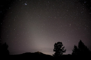 Mountainous horizon, trees in foreground, and zodiacal light extending upward into star field.