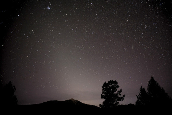 Hazy pyramid of zodiacal light with trees and mountain silhouettes.
