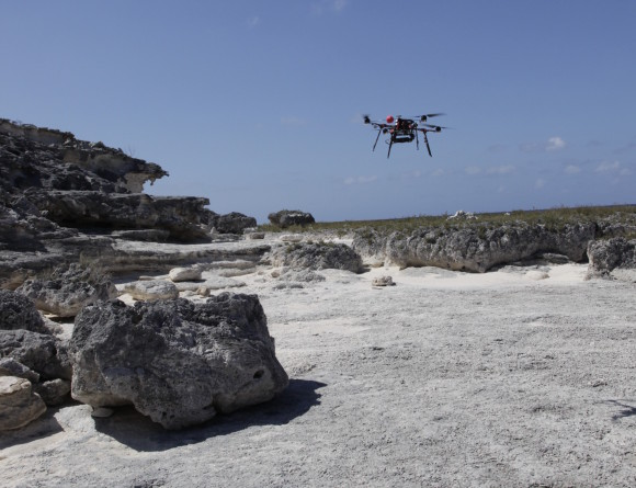 UAV hovering over exposed Pleistocene reef on West Caicos Island prior to climbing to acquisition height (50 m above outcrop). The UAV is manually launched and then controlled by a combination of manual and automated radio signals. Photo by Chris Zahm.