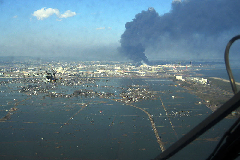 An SH-60F helicopter assigned to the Chargers of Helicopter Antisubmarine Squadron (HS) 14 from Naval Air Facility Atsugi flies over the port of Sendai to deliver more than 1,500 pounds of food to survivors of an 9.0 magnitude earthquake and a tsunami.