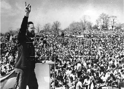 Bearded man at podium passionately addressing huge crowd, right arm pointing up.