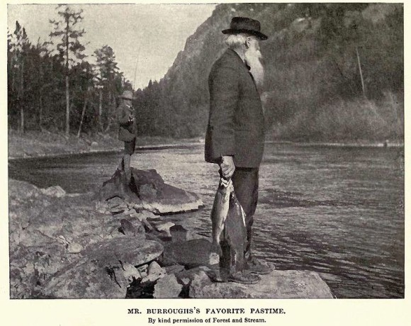 White-bearded man standing by a mountain stream with two large fish dangling from his hand.