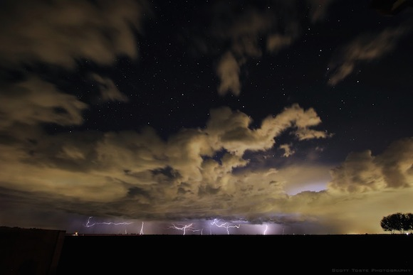 Stars above, clouds lit from below, many faraway lightning strikes.