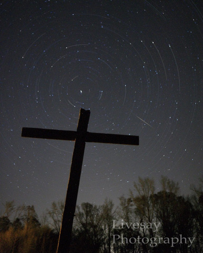 Faint, short concentric streaks of light with one thin straight streak. Big cross in foreground.