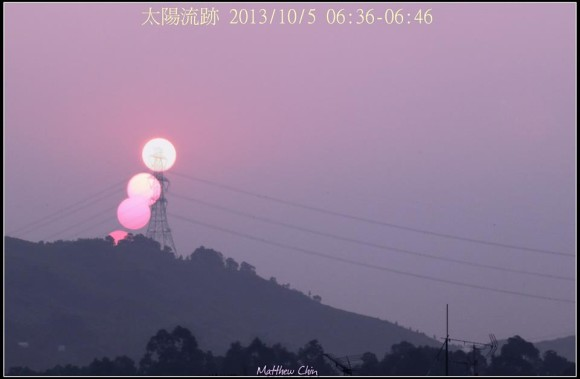 Pink sky with three images of the sun in a line behind a power line pylon.