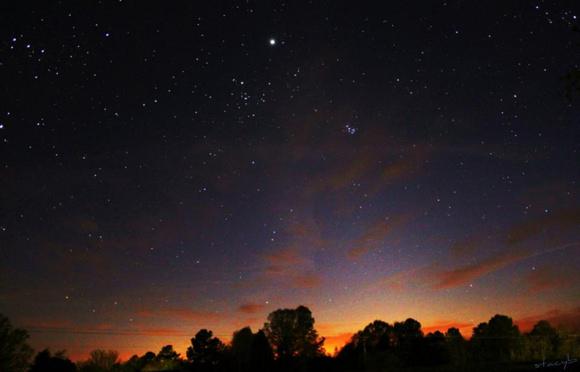 Stars in deep blue sky over orange horizon.