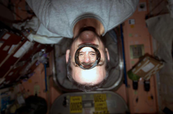 Commander Chris Hadfield looks through a drop of water as they both float on board the International Space Station. Photo credit: NASA