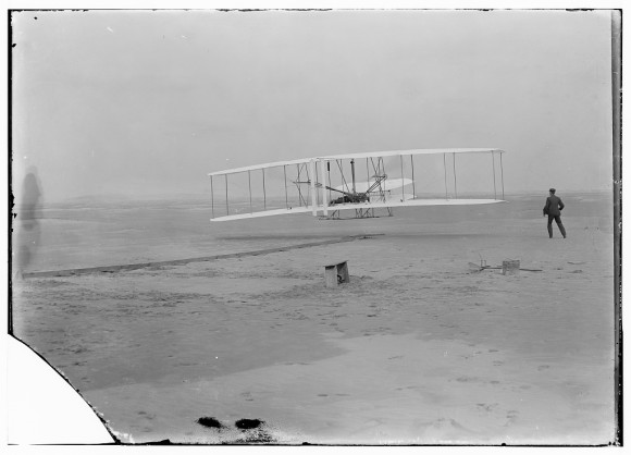 The Wright brothers' airplane on its first powered flight on December 17, 1903.  Via Library of Congress.
