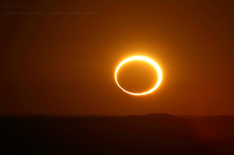Deep orange sky, brilliant yellow ring nearly filled with very dark orange.