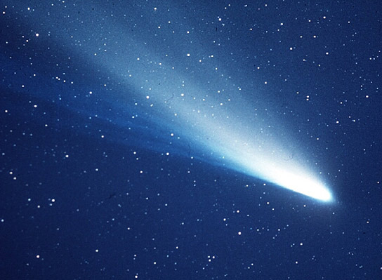 Bright white comet with wide glowing tail streaming out from it.