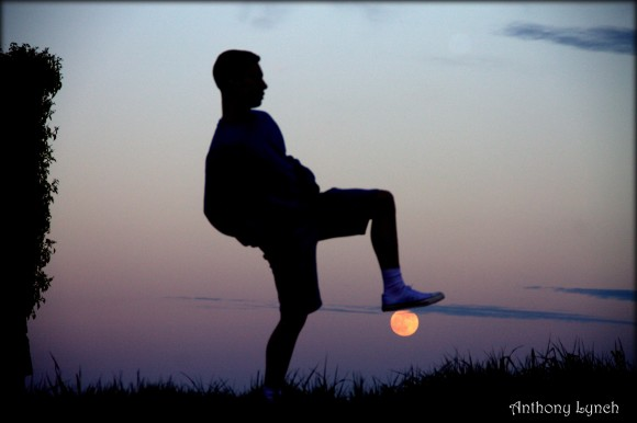 Silhouetted man standing with raised foot apparenly resting on the just-risen full moon.