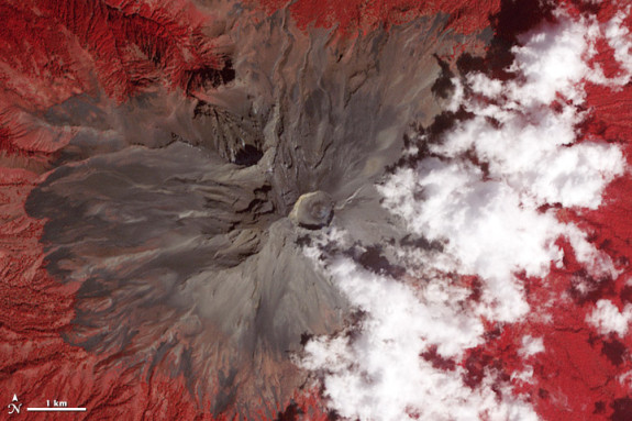 Popocatepetl, a volcano that looms on the Mexico City horizon, has been spitting small amounts of ash, steam, and volcanic gases for most of the 21st century. This satellite image shows the volcano's summit in false-color (near-infrared, red, and green light). Bare rock is brown, vegetation is red, and clouds are white. A very faint volcanic plume is visible in the center of the summit crater. The image was collected on February 5, 2013 by the Advanced Spaceborne Thermal Emission and Reflection Radiometer (ASTER) on the Terra satellite.