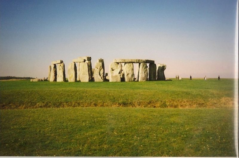 View across a ditch toward massive standing stones of Stonehenge.