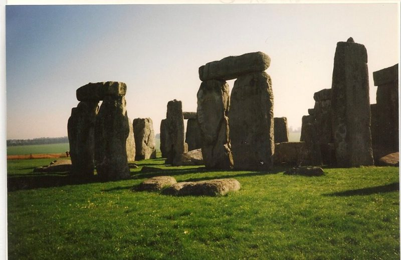 A portion of Stonehenge, with massive upright stones and long shadows.