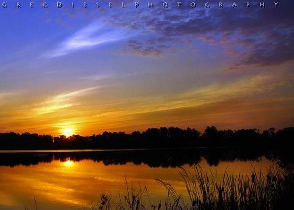 Orange-yellow sunrise under dark blue sky reflected in water.