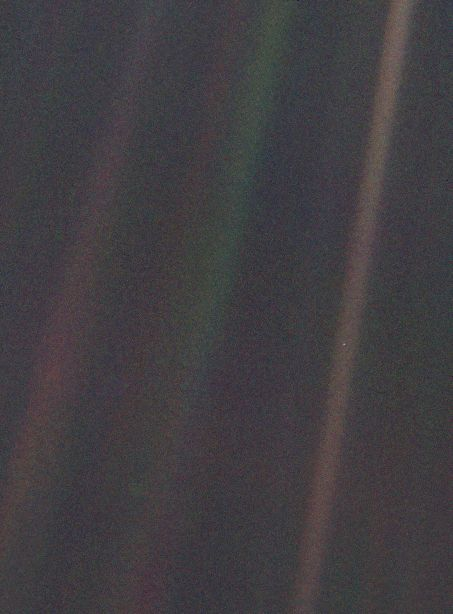 This narrow-angle color image of the Earth, dubbed 'Pale Blue Dot', is a part of the first ever 'portrait' of the solar system taken by Voyager 1. The spacecraft acquired a total of 60 frames for a mosaic of the solar system from a distance of more than 4 billion miles from Earth and about 32 degrees above the ecliptic. From Voyager's great distance Earth is a mere point of light, less than the size of a picture element even in the narrow-angle camera. Earth was a crescent only 0.12 pixel in size. Coincidentally, Earth lies right in the center of one of the scattered light rays resulting from taking the image so close to the sun. This blown-up image of the Earth was taken through three color filters -- violet, blue and green -- and recombined to produce the color image. The background features in the image are artifacts resulting from the magnification.  Image Credit: NASA/JPL