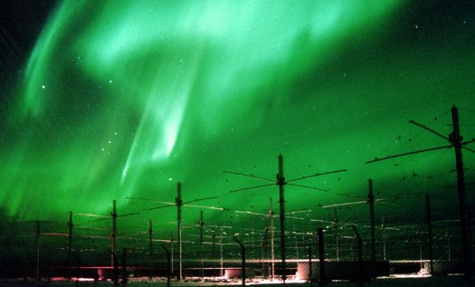 HAARP's antenna array, with the aurora borealis or northern lights in the background. Image via U.S. Naval Research Laboratory
