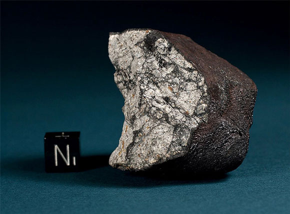 An irregular, shiny rock with a small cube next to it labeled N 1.